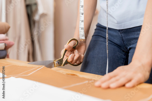 Photo Dressmaker cuts scissors pattern dress detail on sketch lines for sewing machine