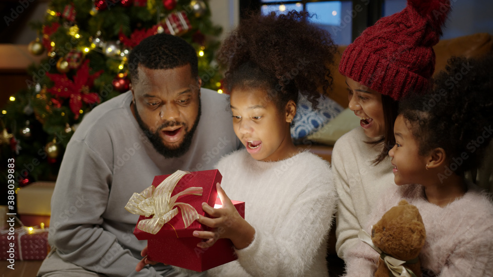 Fototapeta Christmas day, Happy black family at home. African american father, mother and child opening shine light xmas gift box. Cute daughter feeling excited and happy with present.