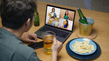 Attractive Young Happy Asian Man Enjoy Relax Night Party Event Online Celebration Festive With Friends At Home Clinking Beer With Glass And Bottle Toasting Drinking Via Video Call.