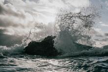 Waves Crashing Against Rocks With Sun Shining Through