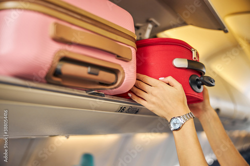 Obraz Hands laying down a carry-on baggage on an upper shelf - fototapety do salonu