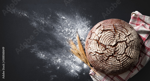 Fototapeta Freshly baked traditional loaf of bread on rustic table obraz