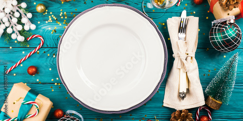 Obraz Festive christmas table setting concept with ornament and gift boxes around. Holiday flat lay with empty dish for text - fototapety do salonu