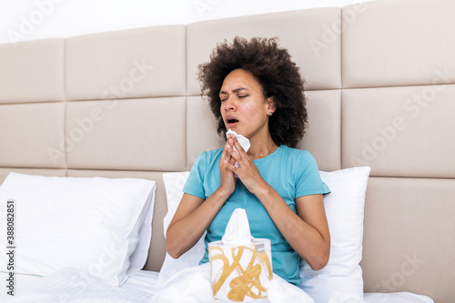 Ill african young woman covered with blanket blowing running nose got fever caug Fototapeta