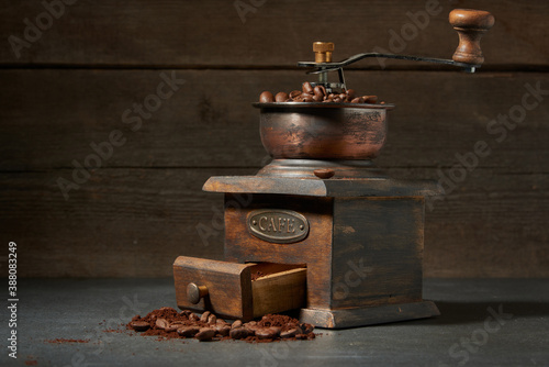 Old vintage grinder with roasted coffee beans and grind coffee in tin jar with scoop over black table with black wooden background Canvas