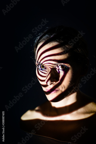 Portrait of a woman illuminated with a projected light in a spiral shape Wallpaper Mural