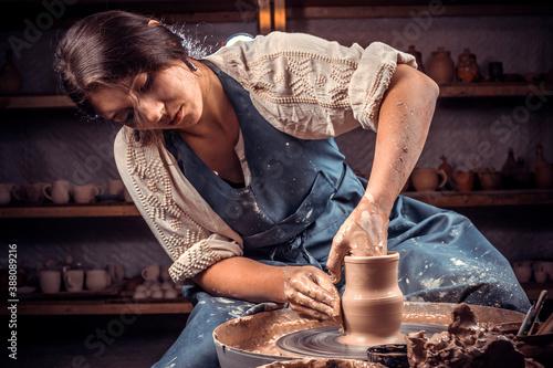 Fotografija Charming pottery master making ceramic pottery on wheel