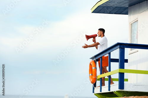 Fotografia, Obraz Male lifeguard with megaphone on watch tower against blue sky