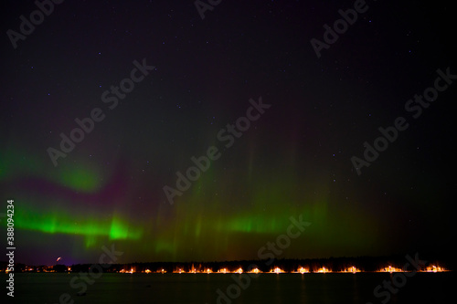 Dark night Green Aurora borealis lights with purple tail beside a lake under starry sky with reflection in scandenavia