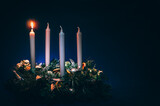 first advent candles burning on black background