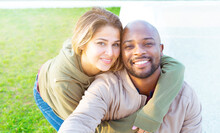 Happy Group Of A Multiethnic Bolt Man And A Caucasian Woman Taking A Selfie Sitting On A Bench In A Park During Autumn Holidays.smiling Interracial Couple Of A Boy And Girl Taking Self Portrait Photo