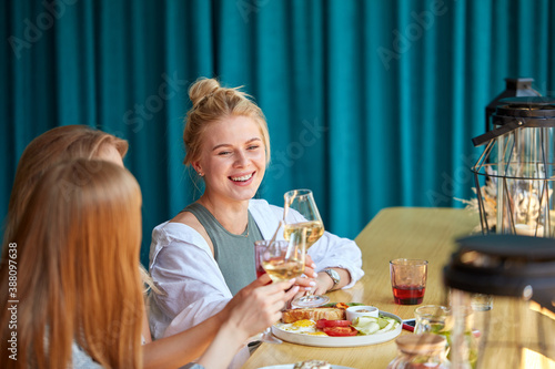 three charming ladies at meeting in restaurant, they have a great time, smile an Canvas Print