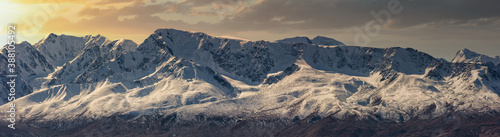 Fotografering Scenic panoramic aerial view of snowy mountain peaks and slopes of North Chuyskiy ridge at sunset