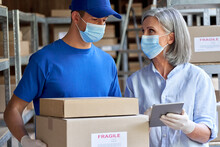 Female Manager Supervisor Wearing Face Mask Using Digital Tablet Talking To Male Courier Holding Shipping Parcels Boxes Discuss Delivery Walking In Warehouse. Covid 19 Safety Social Distance At Work.