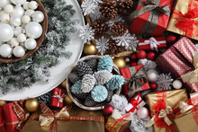 Top View Christmas Decorations Centerpiece With Garland And Balls Near A Basket With Colorful Pine Cones Isolated On Gift Wrapped Packages