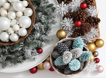 Top View Christmas Decorations Centerpiece With Garland And Balls Near A Basket With Colorful Pine Cones Isolated On A White