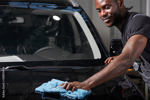 Obraz afro american auto mechanic man wipes the perfect surface of the machine after polishing, preparing a car for owner after repair - fototapety do salonu