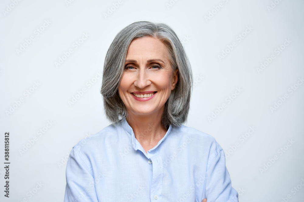 Fototapeta Smiling beautiful mature business woman standing isolated on white background. Older senior businesswoman, 60s grey haired lady professional coach looking at camera, close up face headshot portrait.