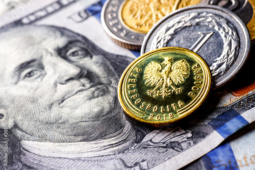 Obraz United States of America banknotes and Polish coins lie together, close-up of metal banknotes of Poland zloty together in paper banknotes of America.World economic crisis associated with coronovirus. - fototapety do salonu