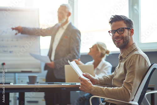 Young cheerful male office worker smiling at camera while having a meeting with Wallpaper Mural