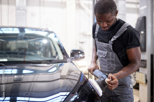 car detailing and polishing concept. young african professional car service male worker, auto mechanic with orbital polisher,automobile concept
