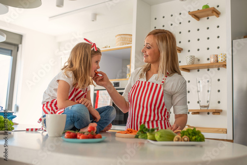 Obraz Mother and cute little daughter having fun in the kitchen while preparing salad together - fototapety do salonu