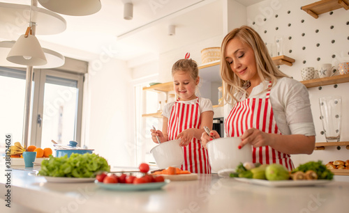 Papel de parede Happy smiling mother and cute little daughter having fun in the kitchen while pr