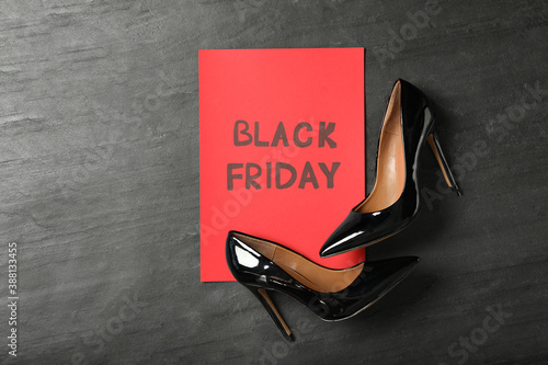 Elegant shoes and sheet of red paper with words Black Friday on dark background, flat lay Poster Mural XXL