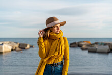 Thoughtful Woman Wearing Sun Hat While Looking Away Against Sea