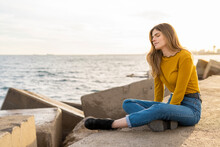 Young Woman With Eyes Closed Sitting And Enjoying Near Sea Against Sky