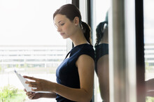 Businesswoman Reading Documents While Standing By Window In Office