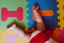 Legs Of Baby Girl Lying On Colorful Puzzle Playmat At Home