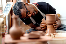 Close-up Of Male Artist Making Earthenware On Pottery Wheel In Workshop