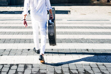 Flamenco Guitarist Holding Guitar While Crossing Road In City