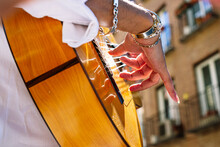 Man Plucking Guitar String Whi...