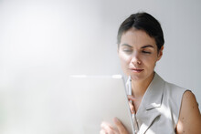 Thoughtful Businesswoman Using Digital Tablet At Office
