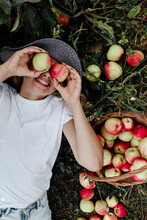 Smiling Woman Holding Apples In Front Of Eyes While Lying On Land At Orchard
