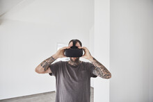 Mature Man Wearing Virtual Reality Simulator While Standing In New House