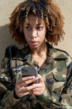 Army Soldier Looking Away While Text Messaging On Smart Phone