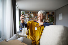 Smiling Senior Woman Taking Selfie With New Blouse On Smart Phone While Sitting At Home