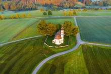 Germany, Bavaria, Etting, Drone View Of Saint Andrew Church Surrounded By Green Fields At Dawn