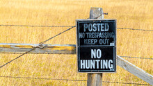 A No Hunting Sign Posted On A Weathered Wooden Barbed Wire Fence In A Field Of Golden Wild Grasses With Copy Space