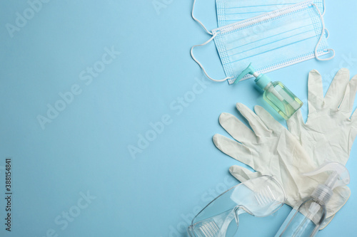 Obraz Flat lay composition with medical gloves, masks and hand sanitizers on light blue background. Space for text - fototapety do salonu