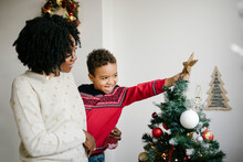 Mother And Son Decorate A Chri...