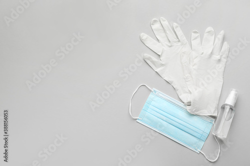 Obraz Medical gloves, protective mask and hand sanitizer on grey background, flat lay. Space for text - fototapety do salonu