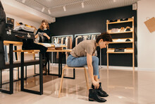 Woman Trying On Boots In Store