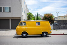 An Older Yellow Van Parked On The Street