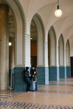 Asian Couple Standing In An Old Train Station Hallway