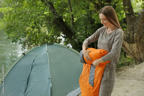 Tela Young woman rolling sleeping bag near camping tent outdoors