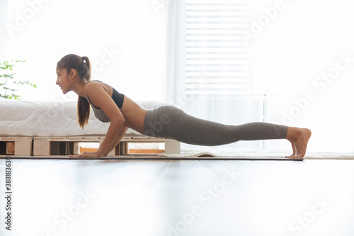 Valokuva Attractive Asian woman practice yoga Plank pose to meditation in bedroom after w